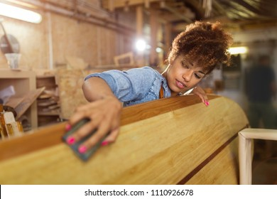 Happy young woman working on surfboard in her workshop