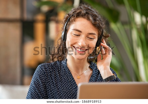 Happy young woman working on laptop while talking to customer on phone. Consulting corporate client in conversation with customer using computer. Service desk consultant talking in a call center.
