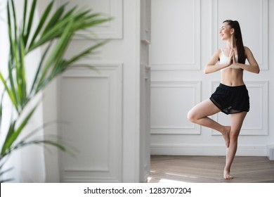 Happy young woman working out indoors, doing yoga exercise, standing in Vrksasana Posture, Tree Pose. Fitness girl.