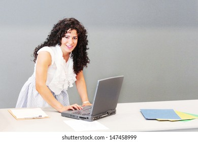 Happy young woman works on her laptop