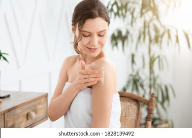 Happy young woman wrapped in towel using body nourishing cream or lotion. Pretty lady using moisturizer for her smooth and silky skin after morning shower, rubbing her shoulder, copy space, sun flare - Shutterstock ID 1828139492