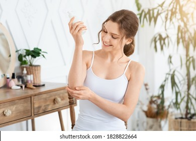 Happy young woman wrapped in towel using body nourishing cream or lotion for her elbows. Pretty lady using moisturizer for her smooth and silky skin after morning shower, copy space, sun flare