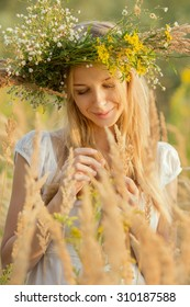 happy young woman in a wreath from a grass