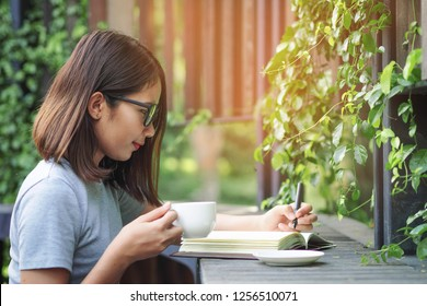 Happy young woman writing on notebook in the park