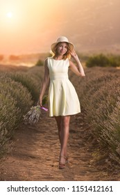 Happy young woman in a yellow dress with a bouquet of lavender in a lavender field