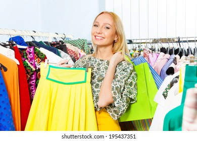 Happy young woman with yellow skirt in the shop