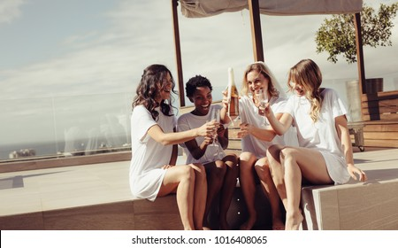 Happy young women drinking champagne at bachelorette party on rooftop. Bride and bridesmaid having fun at hen party.