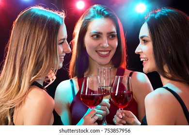 Happy young women with glasses of wine.