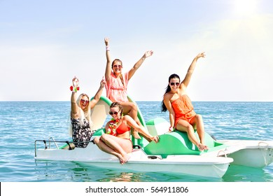 Happy young women having fun raising arms smiling on rental pedalos in blue ocean - Best female friends boat party and sunny  joyful moment together - Concept of summer holiday and teenage friendship
