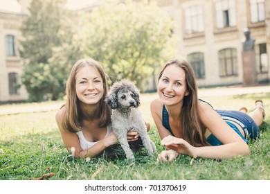 Happy young women hugging dog and  relaxing in the park.
