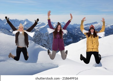 Happy young women jumping in winter in the mountains in the snow