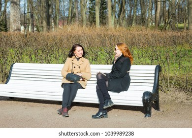happy young women sitting on a banch and speaking in Oranienbaum park