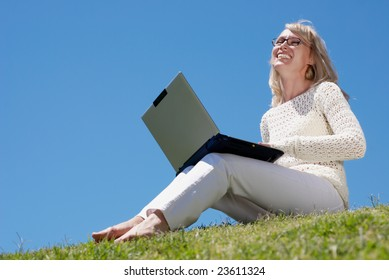 Happy young women smiling and working on a laptop outdoors