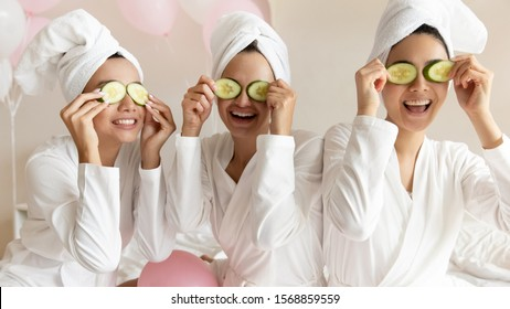Happy young women wear white bathrobes towels on head make cucumber facial skin care mask on eyes laughing relaxing together, smiling girls friends having fun on spa beauty salon party with balloons