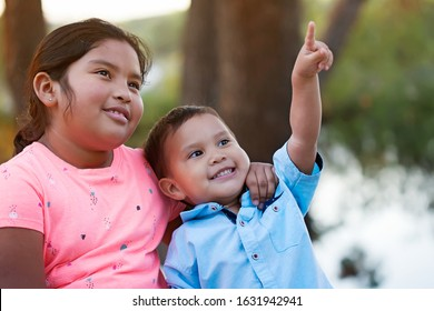 A happy younger brother looks and points to the sky while his older sister puts her arm around his neck and smiles.