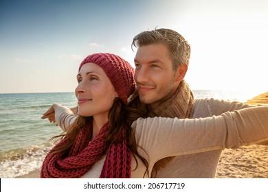 happy younger parents enjoying sundown seaside on the coast
