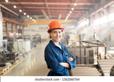 Happy younh successful female worker of factory in workwear and helmet crossing her arms on chest while standing in front of camera