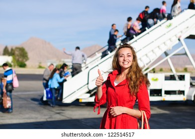 Happy your woman near the airship before on boarding in red coat