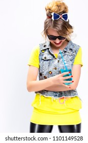 Happy Youth Lifestyle Concepts. Shy and Smiling Caucasian Blond Girl With Cup of Blue Cocktail. Posing in Denim Vest and Sunglasses.Vertical Image