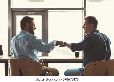Happy youthful guys cooperating together at work in office