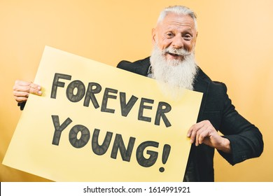 Happy youthful senior feeling forever young - Hipster mature man giving message with yellow banner - Elderly people lifestyle and positive emotions concept