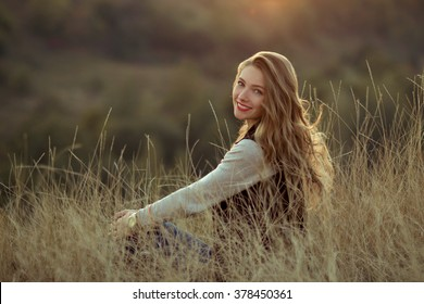 Happy,cheerful,joyful,smiling girl sitting on the hill with very incredibly,beautiful view,watch sunset.Beautiful girl sitting outdoor,in mountains,sunlight,sunny field.Attractive girl with nice smile