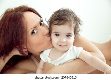 happy-looking baby and  beautiful mother playing together on the bed