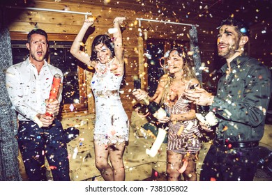 Happy-looking people using party crackers and opening champagne during party.