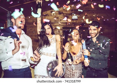 Happy-looking people using party crackers with confetti and opening champagne during party.