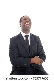 A happyly laughing African American man sitting on a chair with his