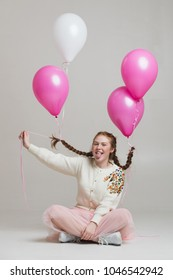 Happyness Red-haired girl with balloons sits on cyclorama