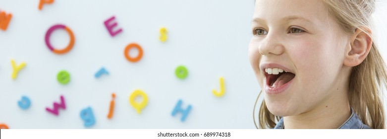 Happy,smiling child learning correct pronunciation - panorama with copy space