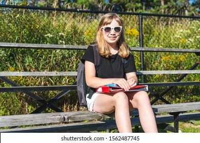 Happy/smiling teen girl sitting on a set of bleachers near her school football/soccer field while wearing sunglasses.