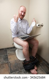 A happy/successful man on the toilet with his computer