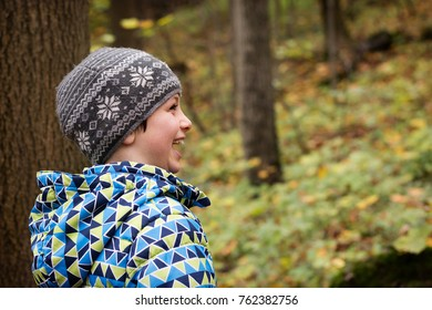 Happz laughing child in a forest, portrait, profile view.