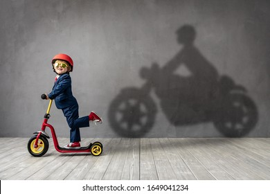 Hapy child wants to become a driver. Funny kid dreams of becoming a pilot. Imagination and motivation concept
