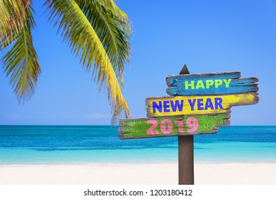Hapy new year 2019 on a colored wooden direction signs, beach and palm tree background