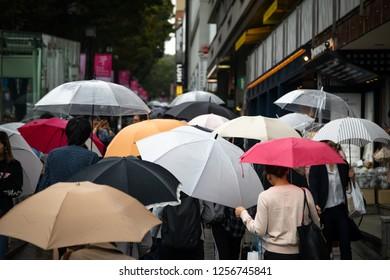 Harajuku Shibuya, Tokyo - Japan - October 5 2018: Pedestrians with umbrellas on a Japanese sidewalk during a rainy afternoon