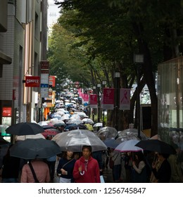 Harajuku Shibuya, Tokyo - Japan - October 5 2018: Telephoto view down a Japanese sidewalk crowded with pedestrians carrying umbrellas during a rainy afternoon