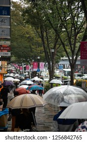 Harajuku Shibuya, Tokyo - Japan - October 5 2018: Telephoto view down a Japanese sidewalk, crowded with pedestrians carrying umbrellas on a rainy afternoon
