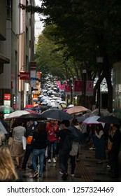 Harajuku Shibuya, Tokyo - Japan - October 5 2018: Telephoto view of a Japanese sidewalk, crowded with pedestrians and  umbrellas on a rainy afternoon