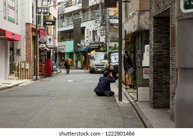 Harajuku, Tokyo / Japan - June 2018:  A model poses for a photographer in the early morning on an empty Takeshita Street before the shopping crowds arrive.