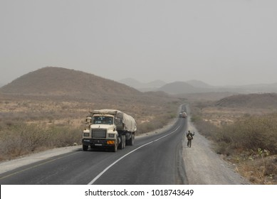 HARAR , ETHIOPIA - MARCH 27 2012: Heavily loaded truck passes by unidentified pedestrian on road near Harar, Ethiopia. Through Harar passes a road linking Somalia and Ethiopia.
