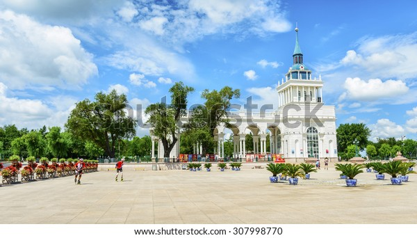Harbin, China - August 10, 2015: Building of People's Square. Located near Harbin Planning Exhibition Hall and Songhua River. People are roller skating. Located in Harbin, Heilongjiang, China.