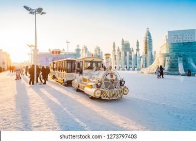 Harbin, China - January 3, 2019: Ice building and pleasure train. China Harbin Ice and Snow World. People are visiting. Located in Harbin, Heilongjiang, China.