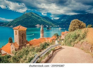 Harbor and ancient buildings in sunny day at Boka Kotor bay (Boka Kotorska), Montenegro, Europe. Retro toned image.