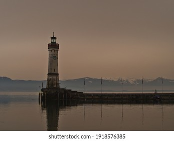 Harbor basin with famous historic Lindau lighthouse on the coast of Lake Constance, Germany. Orange colored sky due to rare weather phenomenon, when desert sand particles of Sahara are in the air.