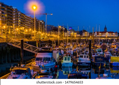the harbor of blankenberge by night with many docked boats, beautiful city scenery, Belgium, 15 february, 2019