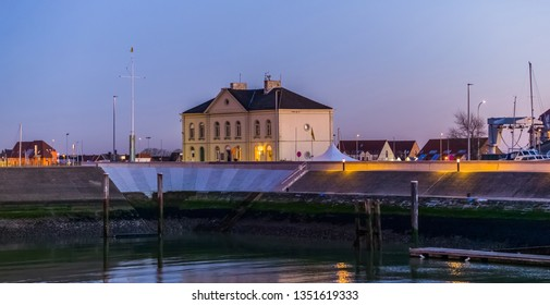 the harbor of blankenberge lighted at night, white building and houses, popular city architeture