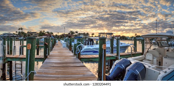 Harbor with boats at golden hour as day breaks over the North Gulf Shore Harbor along the Village at Venetian Bay at sunrise in Naples Florida.